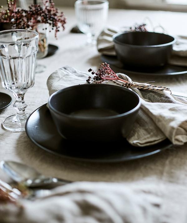 مشهدان لإعدادات طاولة مغطاة بالكتان، يحتوي كل منهما على إناء باللون الرمادي-الأزرق على طبق مع كأس زجاجي ومنديل مربوط.