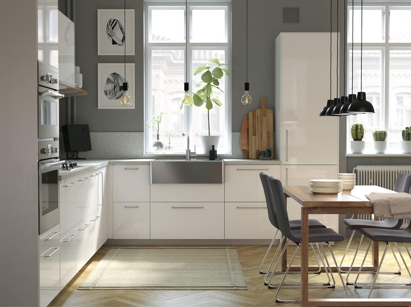 مطبخ عصري زاهي METOD من ايكيا، به أبواب وأدراج RINGHULT بيضاء، مع حوض ستنلس ستيل، في مساحة جلوس مفتوحة.