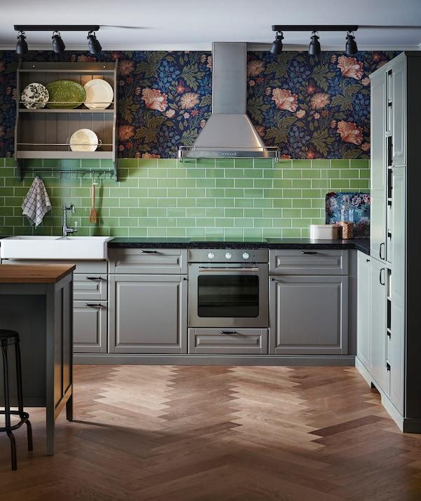 مطبخ به خزائن رمادي، وبلاطات خضراء وورق حائط زهور، مع شفاط ستنلس ستيل.