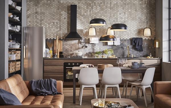 مطبخ بتصميم مفتوح، ومساحة تناول طعام وغرفة جلوس بها كنبات جلد بني وخزائن مطبخ خشبية داكنة بمحاذاة حائط بلاطات.