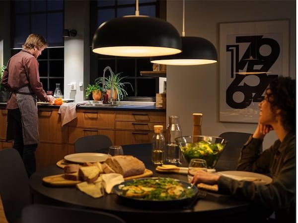 مطبخ مع مصابيح معلقة كبيرة مع إضاءة ذكية وطاولة مهيأة للعشاء وامرأة جالسة على الطاولة ورجل عند الحوض.