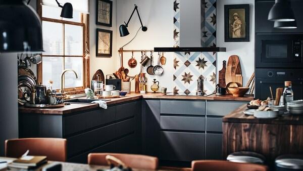 مطبخ METOD حديث بواجهات رمادية داكنة وسطح عمل خشبي مع لوحات حماية لبلاط المطبخ.