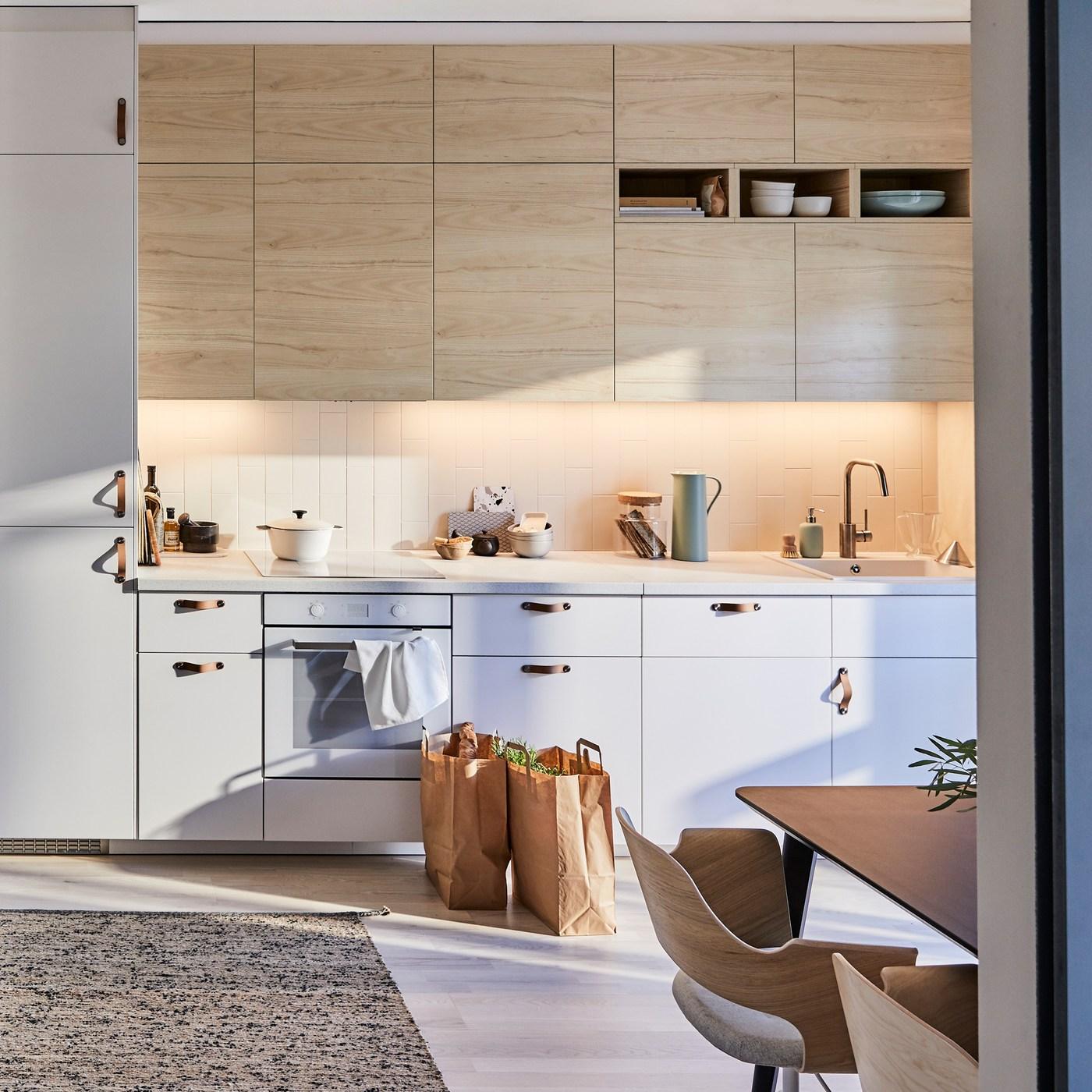 مطبخ METOD من ايكيا بواجهات باب من الخشب الفاتح ASKERSUND بتأثير خشب الدردار مع سجادة حياكة مسطحة MELHOLT مصنوعة من الجوت والصوف.