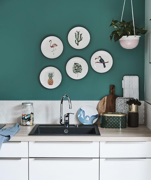 مطبخ صغير مع أسطح عمل من الخشب وحائط أخضر عليه أطباق للزينة.