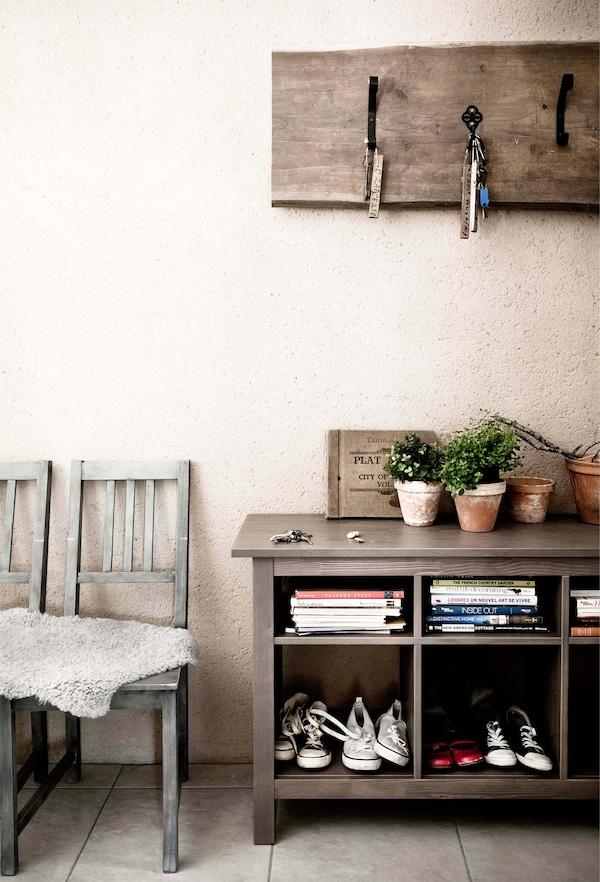Muebles de madera rústicos en una habitación de colores claros con sillas, estantería abierta y percheros sobre la pared.