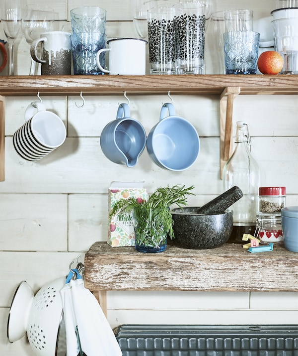 Mugs and cups on a shelf and hanging from hooks above a wooden worktop.