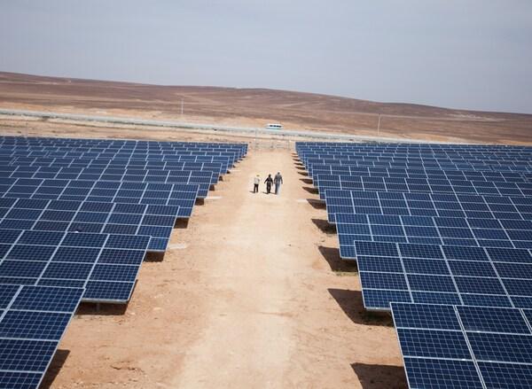 Muitos painéis solares instalados no solo, numa planície árida.
