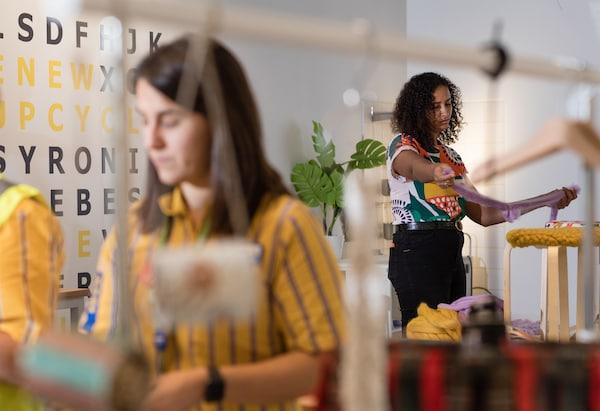 Mujer con una camiseta estampada corta tiras de tela morada para cubrir un taburete de madera. Colaboradora de IKEA trabajando en un proyecto de manualidades.