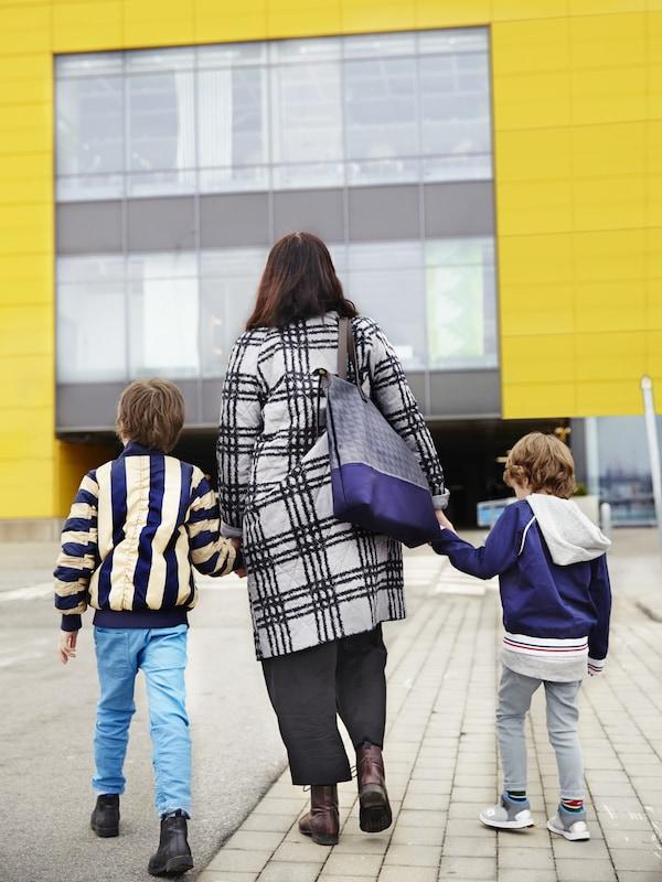 Mujer de la mano con sus dos hijos caminando abrigados hacia la tienda amarilla IKEA.