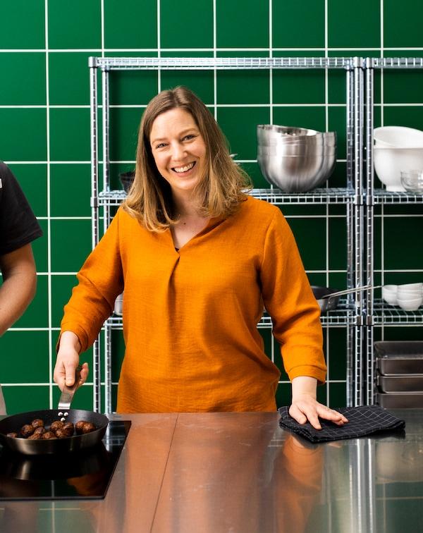 Mujer de pie en una cocina de acero inoxidable y azulejos verdes en la pared, mientras sujeta una sartén con albóndigas vegetales.