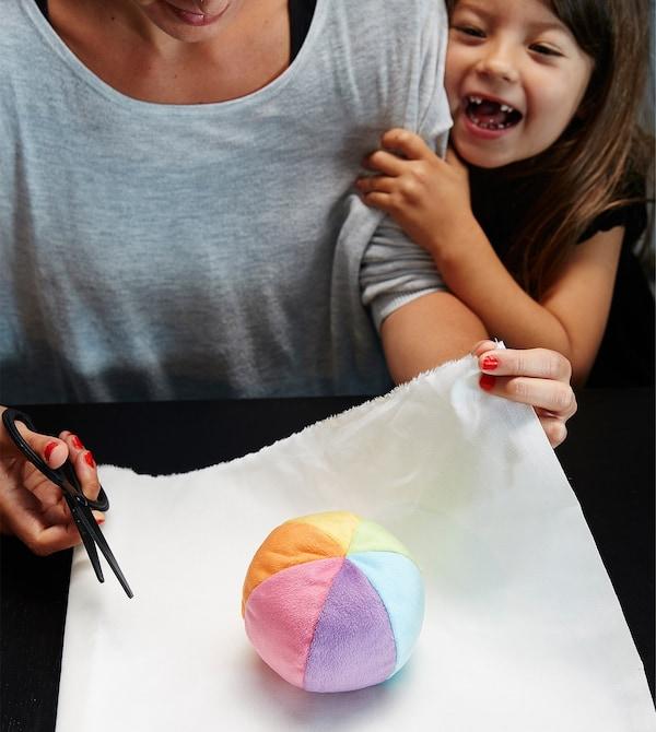 Mujer envolviendo una pelota de peluche con un mantel blanco ante la mirada de un niño.