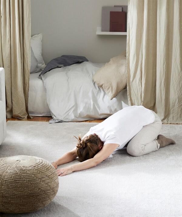 Mulher prostrada, com as pernas dobradas numa posição de exercício, sobre um tapete de sala, com os móveis afastados para o lado em volta dela.