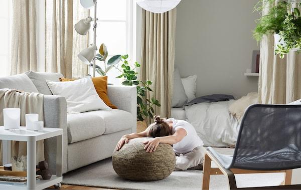 Mulher sentada num tapete de sala, com as pernas dobradas sob si e inclinada, com os braços esticados pousados num pufe.