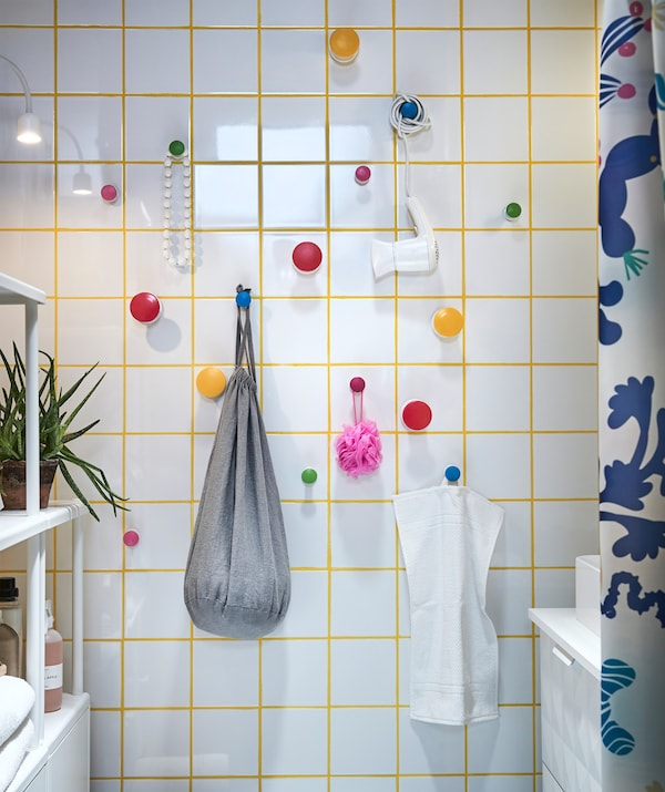 Multi-coloured LOSJÖN hanger knobs in a white tiled bathroom with bathroom accessories hanging from them.