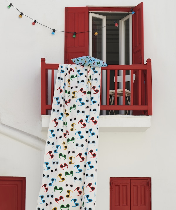 Multicolour fabric with sunglasses print hanging from a red balcony on a white wall, with multicolour string lights.