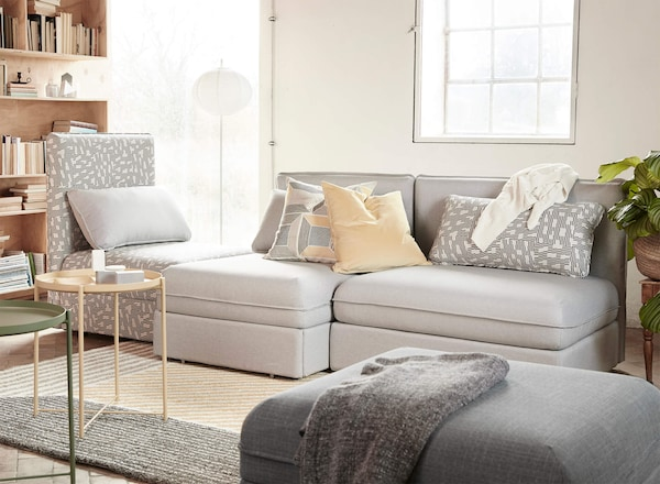 Multiple sofa seat sections in a living room in light gray and a patterned gray, with accent cushions and throw blankets.
