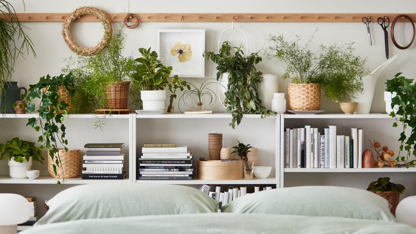 Múltiples plantes en tests, reals i artificials, enmig de llibres i articles decoració als prestatges que hi ha al costat d'un llit amb roba de llit BERGPALM.