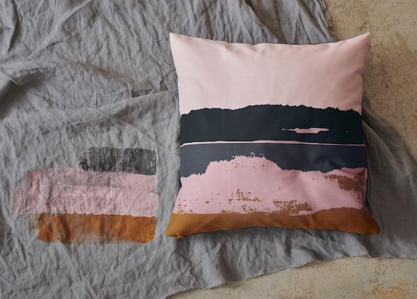 Muodikas ELDTÖREL-tyynynpäällinen, jonka vaaleanpunainen ja tummanharmaa kuvio muistuttaa vesivärimaalausta.