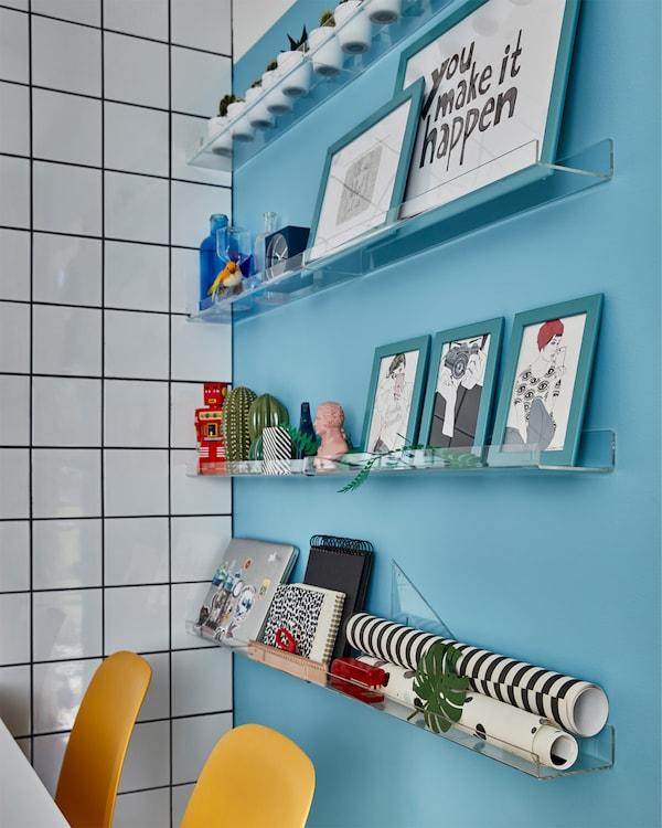 Mur bleu et cimaises transparentes sur lesquelles sont placés des cadres bleus, des objets décoratifs, un ordinateur portable, et plus encore. Devant, des chaises jaunes.