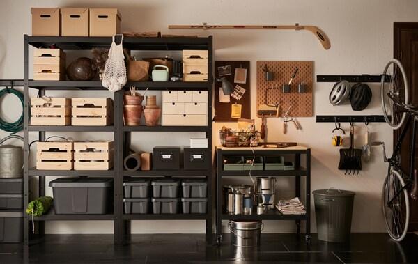 Mur d'un garage avec étagères BROR noires remplies de boîtes en bois, en carton et en plastique de différentesdimensions.
