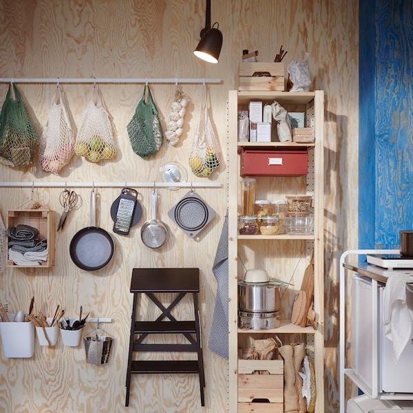 Mur en bois garni de barres avec crochets en finition blanche. Des filets contenant des fruits, des ustensiles de cuisine et un marchepied y sont suspendus.