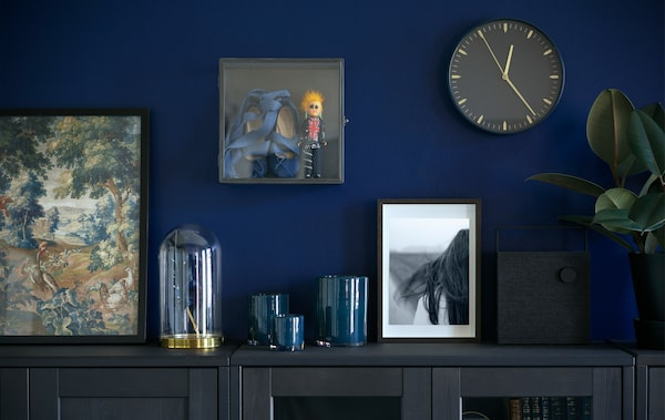 Mur peint en bleu accueillant une horloge, des cadres variés et la vitrine BARKHYTTAN.