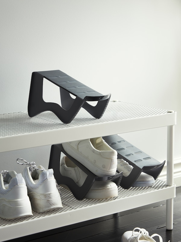 MURVEL shoe organizers maximise the use of space on a white MACKAPÄR shoe rack, holding pairs of white sneakers.