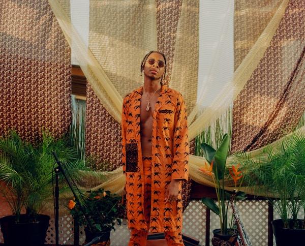 Musician Masego wearing orange clothes.