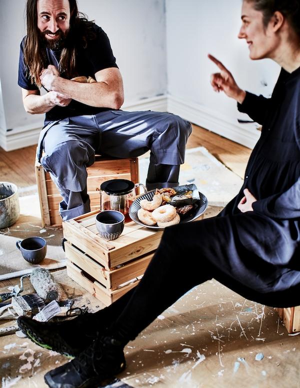 Muškarac i žena gledaju jedno u drugo sa svoje strane stolića uz kavu jednostavno posluženu na drvenim sanducima na kojima i sjede.