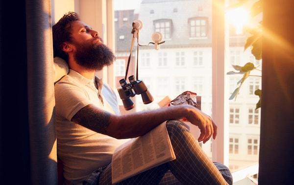 Muškarac sedi na dubokom, osunčanom simsu, opuštene glave, zavaljene unazad. Višespratna fasada u pozadini.