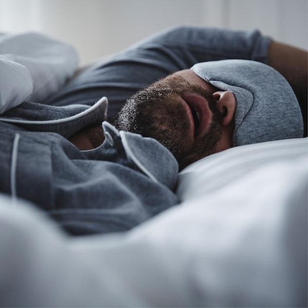 Muškarac u plavoj pidžami s plavom maskom za spavanje spava u krevetu otvorenih usta.