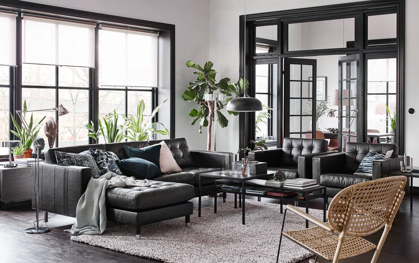 Musta, beige ja valkoinen olohuone, jossa musta nahkasohva divaaneilla ja kaksi lepotuolia vierekkäin.