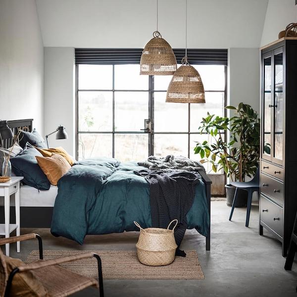 Musta HEMNES-sänky jossa on tummansiniset PUDERVIVA-lakanat, sängyn yläpuolella on kaksi TORARED- kattovalaisimen varjostinta.