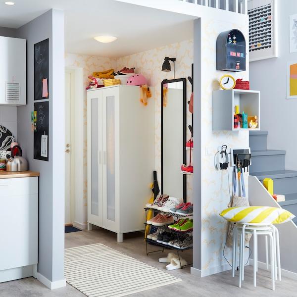 Musta IKEA GREJIG kenkähylly ja valkoinen ANABODA vaatekaappi ovat näppäriä pienen eteisen ratkaisuja.