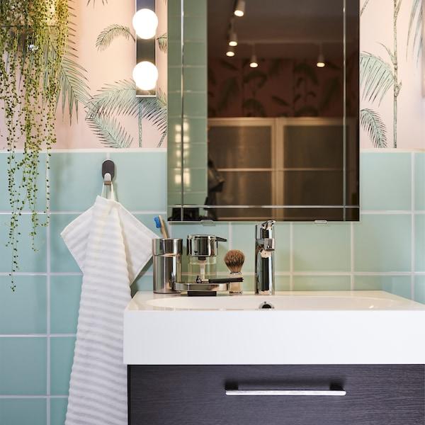 Mustanruskea allaskaluste, valkoinen pesuallas, peili ja peilivalaisin sekä raidallinen pyyhe vaaleanpunaisessa ja vihreässä kylpyhuoneessa.