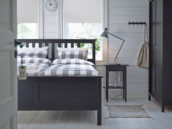 Mustanruskea HEMNES-sängynrunko, joka on pedattu vaaleanharmailla ja valkoisilla ruudullisilla lakanoilla.