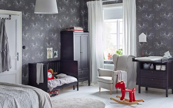 Mustanruskea pinnasänky, vaatekaappi ja hoitopöytä makuuuhuoneen nurkassa, jossa harmaa kuvioitu tapetti.