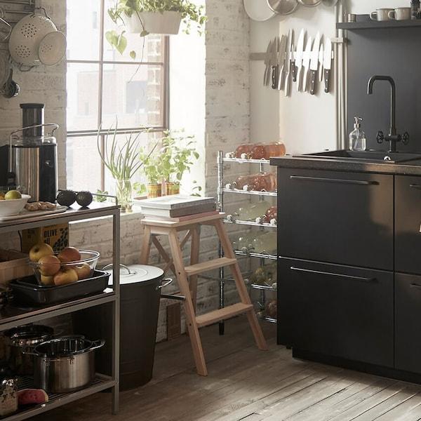Mustat keittiön kaapit, tiskiallas, metallivaunu ja ruoanlaittotarvikkeita, jotka on varastoitu tangolle ikkunan viereen.