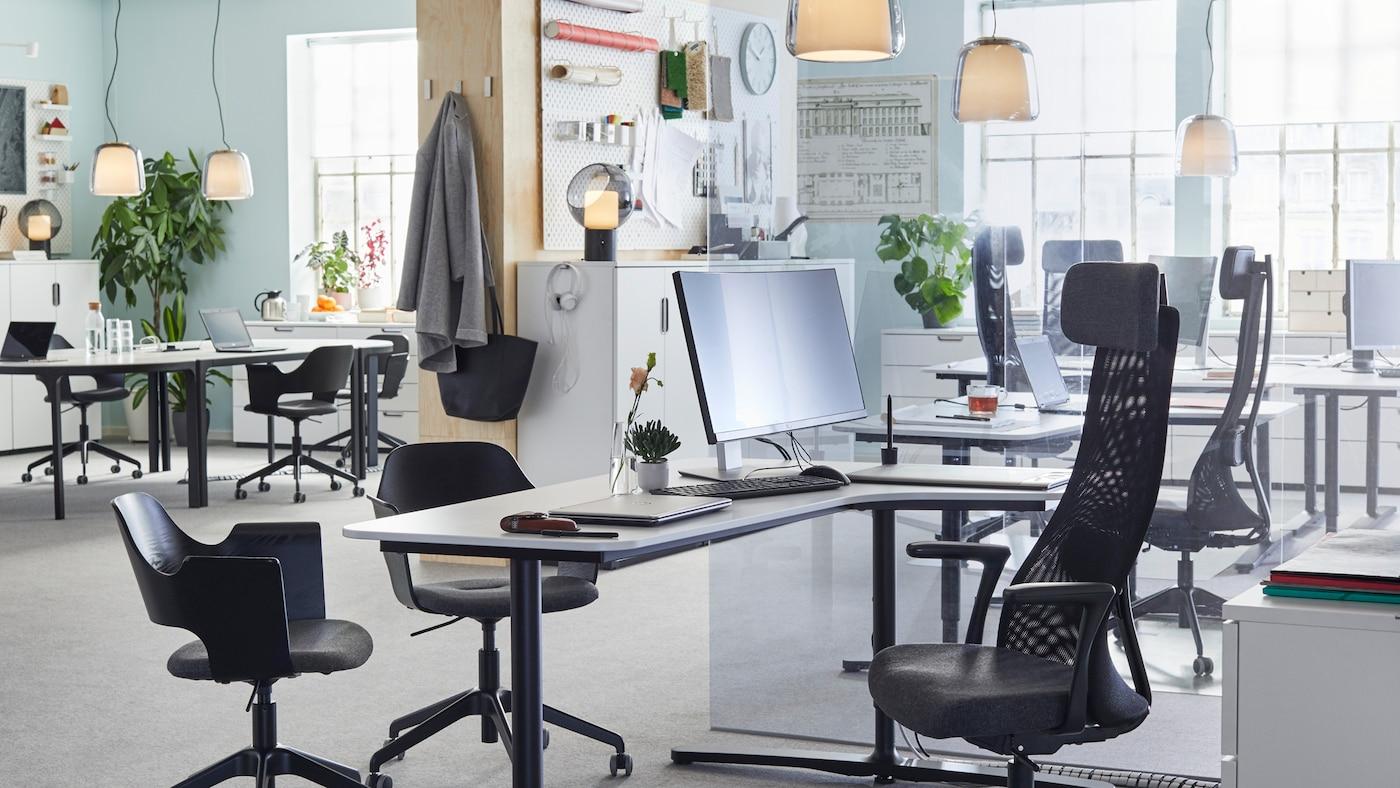 Mustat säädettävät JÄRVFJÄLLET-työtuolit ja sileät valkoiset työpöydät avoimessa ja ilmavassa toimistotilassa.