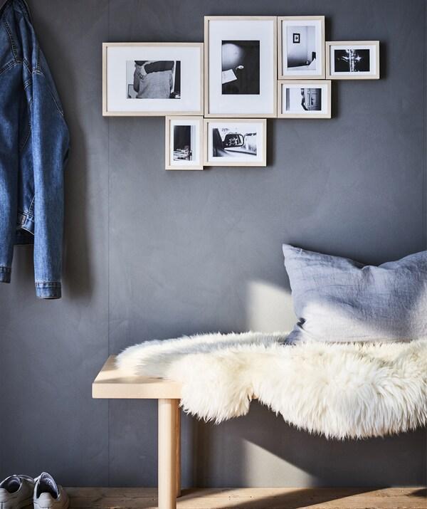 Mustavalkoisia kuvia on aseteltu seinälle lampaantaljalla peitetyn penkin yläpuolelle kauniiseen asetelmaan.