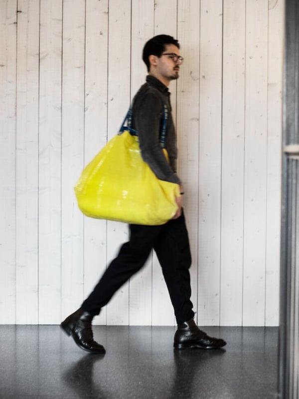 Mustiin pukeutunut mies kävelee IKEA-tavaratalossa kuljettaen keltaista ostoskassia.