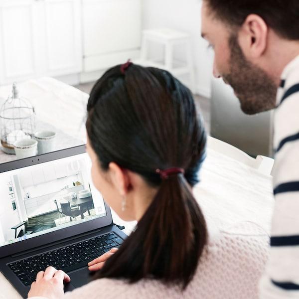 Muž a žena před laptopem používají plánovač kuchyní IKEA.