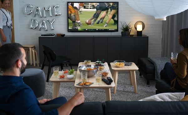 Muž a žena sedia na pohovke a sledujú v televízii ragby s občerstvením v miskách na konferenčných stolíkoch.