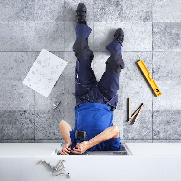 Muž inštaluje spodnú kuchynskú skrinku.