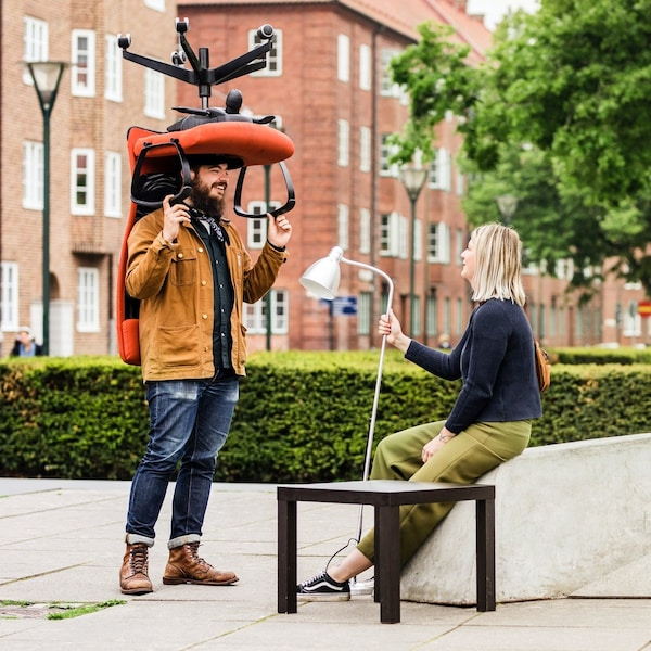 Muž na ulici drží na ramenou kancelářskou židli, žena sedící na zídce oproti němu drťží v rukou lampu.