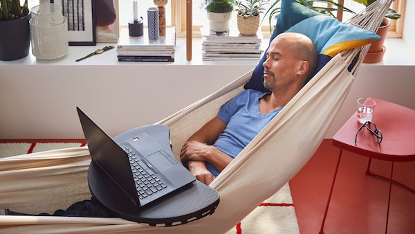 Muž odpočíva v hojdacej sieti s notebookom na lone.