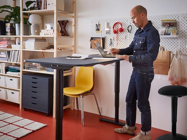Muž po stojačky pracuje pri stole s nastaviteľnou výškou.