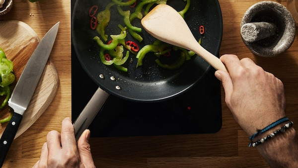 Muž pripravuje vegetariánske jedlo so zelenými a červenými paprikami na prenosnej indukčnej varnej doske TILLREDA.