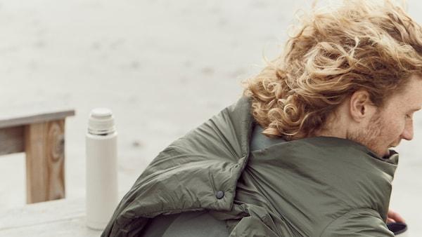 Muž sedí na pláži oblečený v prikrývke FÄLTMAL, ktorú má na chrbte zapnutú pomocou šikovného zapínania.