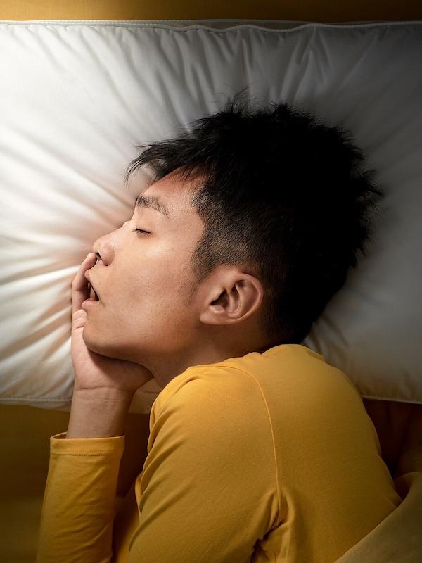 Muž spíci hlubokým spánkem na boku na ergonomickém polštáři.
